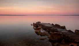 Spiaggia della Croazia di alba con colore pastello Rocky Jetty fotografie stock