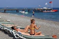 Spiaggia della località di soggiorno di Adalia con le chaise-lounge del sole, l'ancoraggio ed il pe dei sunbathers Immagini Stock Libere da Diritti