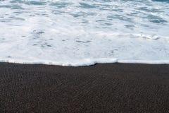 Spiaggia della sabbia nera ed onda vulcaniche del mare immagini stock libere da diritti