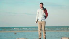 Spiaggia di camminata dell'uomo con il computer portatile attuale stock footage