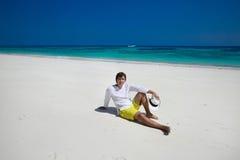 Spiaggia di estate distendasi Riuscito uomo bello in cappello che riposa sulla e Fotografie Stock Libere da Diritti