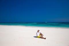 Spiaggia di estate distendasi Riuscito uomo bello in cappello che riposa sulla e Fotografia Stock