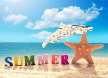 Spiaggia di estate Stelle marine con l'ombrello e lettere su una spiaggia immagine stock