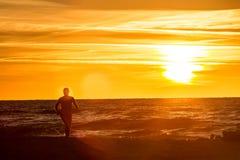 Spiaggia di funzionamento al tramonto Fotografia Stock