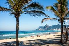Spiaggia di Ipanema e via anteriore con le palme ed il mosaico del marciapiede immagini stock