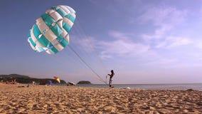 SPIAGGIA di KARON, PHUKET, TAILANDIA, 2 del maggio 2015 Equipaggi la tenuta del paracadute nel vento sulla spiaggia archivi video