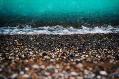 Spiaggia di marea dell'acqua con il ciottolo Immagini Stock