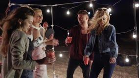 Spiaggia di notte, amici con le tazze di plastica in loro mani che ballano con la colonna sana sul partito con illuminazione