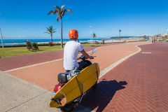 Spiaggia di Rider Scooter Motor Bike Surfboard immagine stock