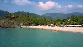 Spiaggia di sabbia al piede delle colline dall'oceano azzurrato video d archivio