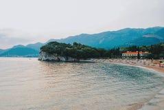 Spiaggia di sabbia con l'albergo di lusso vicino allo Sveti Stefan fotografia stock