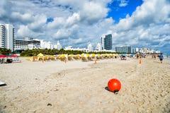 Spiaggia di sabbia con sdraio sotto l'ombrello giallo Fotografia Stock Libera da Diritti