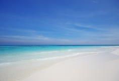 Spiaggia di sabbia e cielo blu bianchi Fotografia Stock