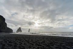 Spiaggia di sabbia nera Reynisfjara in Islanda Rocce in acqua Onde di oceano Giorno ventoso Fotografia Stock