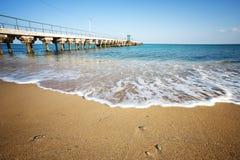 Spiaggia di Sandy con il molo Fotografie Stock