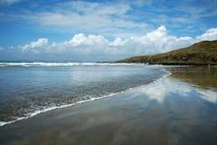 Spiaggia di Sandy e riflessione del cielo e delle nubi Fotografia Stock