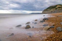 Spiaggia di Seatown e vista del cappuccio dorato il più alto punto sulla costa sud dell'Inghilterra fotografia stock