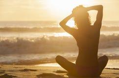 Spiaggia di seduta del bikini di tramonto di alba della ragazza della donna fotografia stock libera da diritti