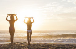 Spiaggia di tramonto dei surfisti & dei surf delle donne del bikini Fotografie Stock Libere da Diritti