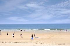 Spiaggia dorata con la gente che va praticare il surfing Immagini Stock Libere da Diritti