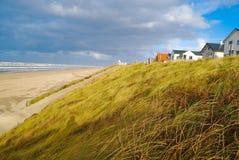 Spiaggia, duna con erba e case Fotografia Stock Libera da Diritti