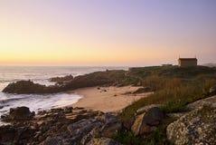 spiaggia e chiesa nell'ambito della luce di orango del tramonto fotografie stock libere da diritti