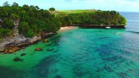 Spiaggia e rocce tropicali con l'oceano del turchese Vista aerea del posto di paradiso in Bali video d archivio