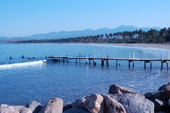 Spiaggia e vecchio pilastro di pesca lungo la linea costiera Fotografie Stock