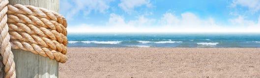 Spiaggia piena di sole con l'intestazione e la corda della sabbia