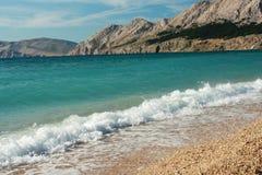 Spiaggia pittoresca piacevole con acqua pulita cristal Fotografie Stock Libere da Diritti
