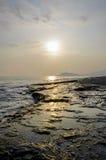 Spiaggia rocciosa al tramonto Fotografie Stock