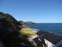 Spiaggia rocciosa della costa della campagna giapponese con costruzione ed i campi Fotografia Stock