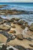 Spiaggia rocciosa di vista sul mare con le grandi rocce e massi beige in acqua di mare calmo fotografie stock