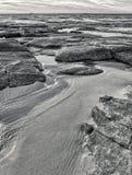 Spiaggia rocciosa di vista sul mare con le grandi rocce e massi nell'immagine in bianco e nero dell'acqua di mare calmo fotografie stock libere da diritti