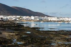 Spiaggia rocciosa e case bianche nell'isola di Graciosa della La Caleta del Sebo fotografia stock