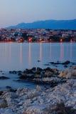 Spiaggia rocciosa e città di Novalja sull'isola del PAG Immagine Stock