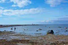 Spiaggia rocciosa e treccia con un piccolo faro Immagine Stock Libera da Diritti