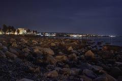 Spiaggia rocciosa illuminata dalla luna Civitavecchia Italia immagini stock