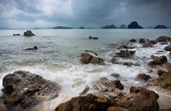 Spiaggia rocciosa turbolenta al tramonto fotografia stock libera da diritti
