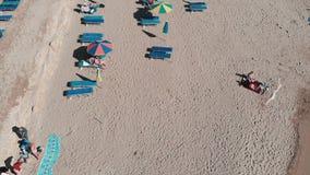 Spiaggia sabbiosa con gli ombrelli ed i lettini Famiglia sulla vacanza Ragazze e ragazzi che si trovano sulla spiaggia Il fuco vo stock footage