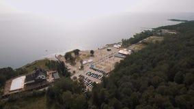 Spiaggia sabbiosa del colpo aereo sulla riva di mare con le tende bianche e la vasta foresta, giorno soleggiato stock footage