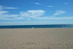 Spiaggia sabbiosa del mare con alcuna gente, i lettini e un ombrello fotografia stock