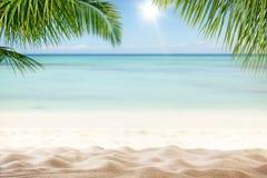 Spiaggia sabbiosa di estate con l'oceano della sfuocatura su fondo Fotografia Stock