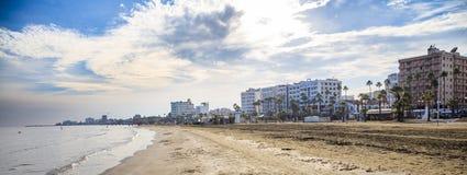 Spiaggia sabbiosa di Finikoudes a Larnaca, Cipro Cielo blu e nuvole bianche per fondo Spazio, insegna Fotografie Stock Libere da Diritti