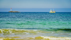 Spiaggia sabbiosa di vista sul mare con il faro sull'orizzonte immagini stock