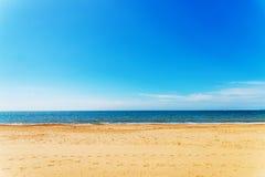 Spiaggia sabbiosa ed oceano blu, bello giorno soleggiato, posto di resto Immagini Stock