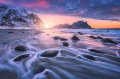 Spiaggia sabbiosa stupefacente con le pietre in acqua vaga al tramonto immagini stock libere da diritti