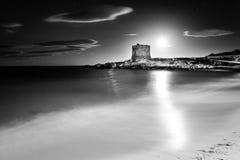 Spiaggia sabbiosa, una torre sulla costa e belle nuvole nel cielo Fotografia Stock