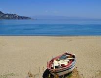 Spiaggia sabbiosa vuota con la barca abbandonata Immagini Stock