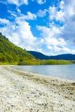 Spiaggia soleggiata pulita incontaminata con le montagne nella distanza Giorno di estate nel lago fotografia stock libera da diritti